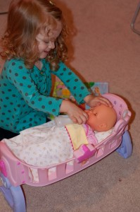 little girl with doll cradle